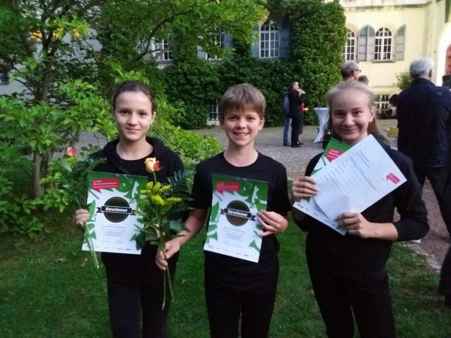 Drei Schüler des Percussionensemble Markkleeberg mit Urkunde und Blume in der Hand